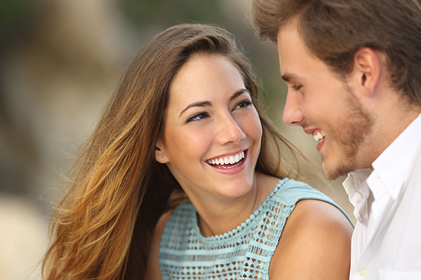 A woman looking at her boyfriend and smiling with white teeth thanks to cosmetic dentistry