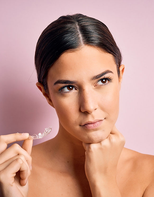 A woman with her hand on her chin holding clear aligners
