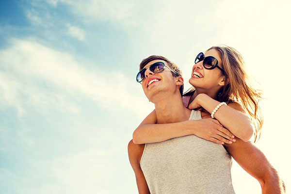 A couple with sunglasses showing off healthy and beautiful white teeth after general dentistry services