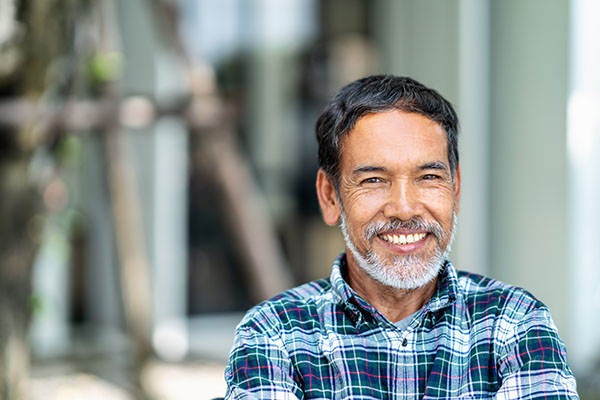 A man with dental implants and restorations in a plaid shirt smiling