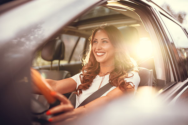 A woman with white teeth and a straight smile driving her car