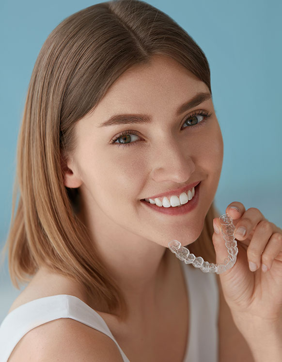 A woman with short hair smiling and holding Invisalign aligners