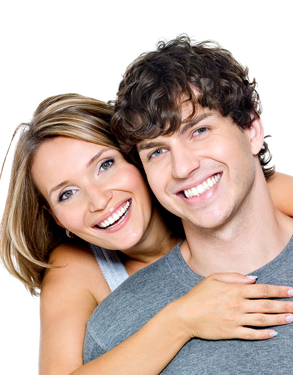 A man and woman smiling with white, straight teeth after visiting our dentist office