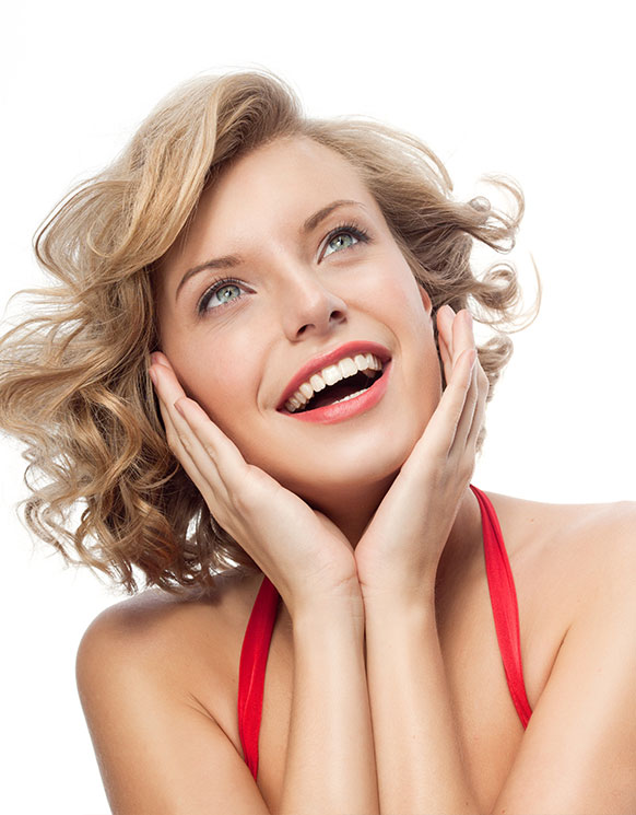 A woman with short curly hair showing off her bright smile after teeth whitening